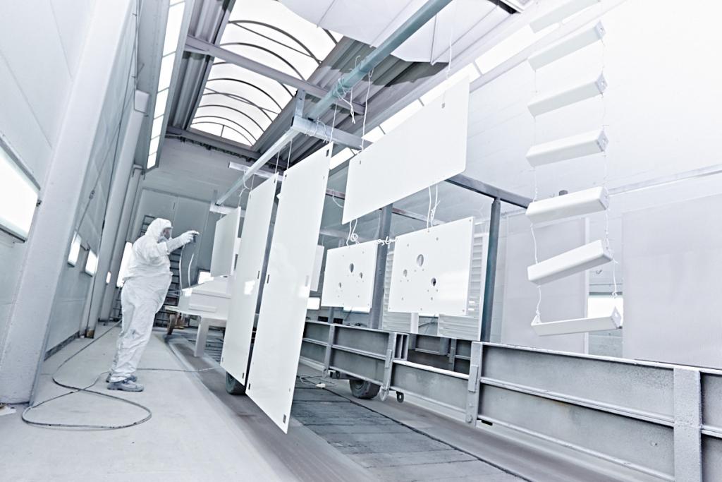 Mitarbeiter der Lackiertechnik beim lackieren von Industrieteilen